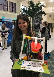 Melissa Spade with an adapted toy made from common materials and communication pictures
